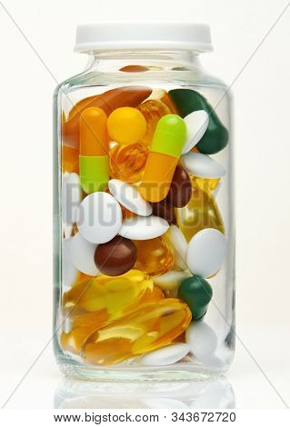 Glass bottle full of colorful pills, tablets, vitamins, drugs, omega 3 fish oil, gel capsules, medicament and food supplement for healthcare. Pharmaceutical industry. Pharmacy. Macro photo.