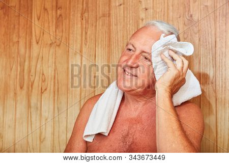 Old man wipes the sweat from his forehead in the sauna at the Wellness Hotel