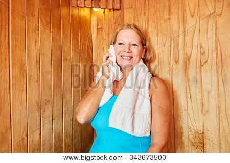 Smiling senior woman sweats in the sauna for health and well-being