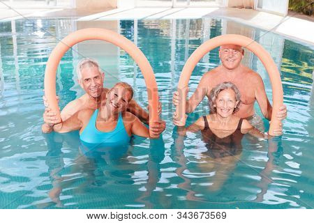 Group of seniors doing water aerobics in a rehab class in the swimming pool
