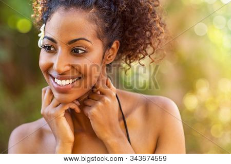 Cheerful african american woman with hand on neck outdoor looking away. Beautiful woman in black bikini at spa resort. Happy latin girl pampering herself with spa treatment.