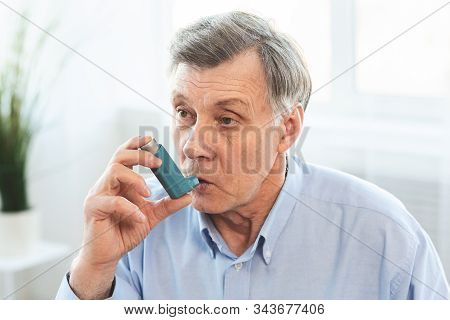 Senior Man Using Asthma Inhaler For Allergies In Modern Clinic, Copy Space