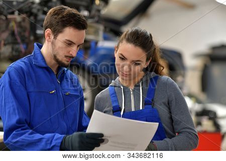 Apprentice working in automobile workshop