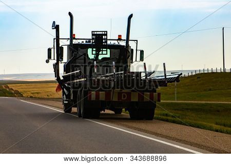 A Rear View Of A Flatbed Industrial Lorry For Transport Of Heavy Cargo And Goods, Parked At Side Of