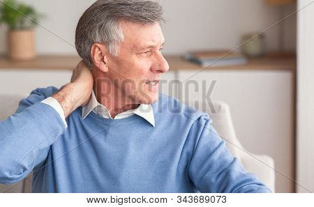 Senior Man Massaging Neck Suffering From Arthritis Pain Sitting On Couch At Home. Selective Focus