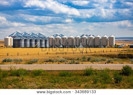 A Wide View Of An Industrial Grain Elevator Complex, With Hopper Bottom Storage Bins And Steel Silos
