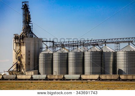 A Wide Angle View Of A Grain Mill And Elevator, Group Of Steel Storage Silos Are Connected To Indust