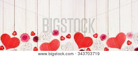 Valentines Day Banner With Border Of Hearts, Flowers And Decor Against A Rustic White Wood Backgroun