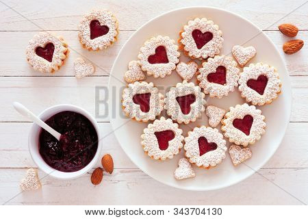 Valentines Day Jam Filled Cookies With Heart Shapes. Top View Table Scene Against A White Wood Backg