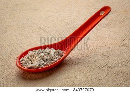 food grade diatomaceous earth detox supplement - red ceramic teaspoon of powder against textured paper