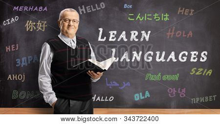 Mature male teacher in front of a blackboard with hello written in different foreign languages and text learn languages