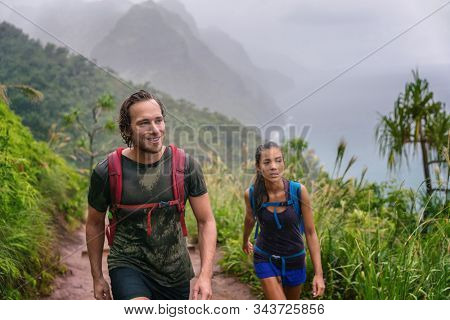 Mountain trek hikers couple walking in rain trekking on trail trek with backpacks healthy active lifestyle. Hiker man happy on hike in nature landscape with Asian girl, Na Pali Coast, Kauai, Hawaii.