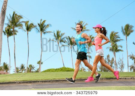 Healthy couple running together happy partner workout training outdoors in tropical city background. Woman and man jogging outside.