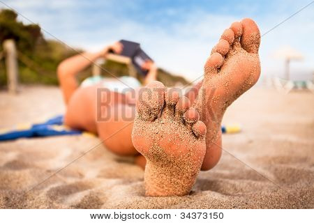 Woman reading a book on the beach.