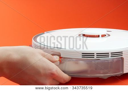 Robot Vacuum Cleaner Replacing A Container With Water. Robot Vacuum Cleaner Isolated On Red Backgrou