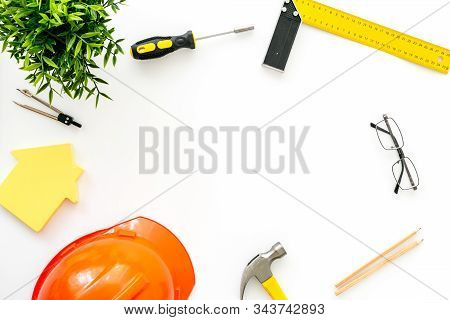 Construction Concept. Helmet, Tools On Work Desk, House Cutout On White Background Top-down Frame Co