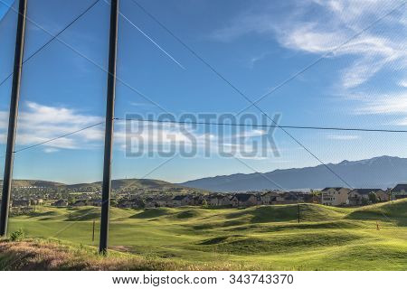 Fence With Scenic View Of Golf Course Houses And Mountain On A Sunny Day