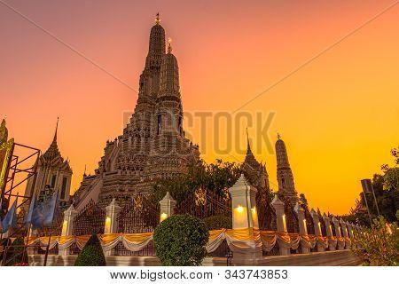 Large illuminated temple Wat Arun after sunset seen accross river Chao Phraya Bangkok, Thailandgold