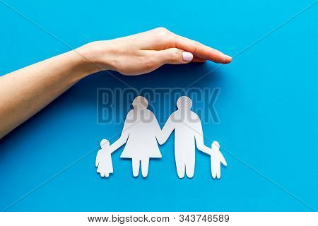 Health Insurance Concept. Family Cutout Under Palms Protect On Blue Background Top-down Copy Space