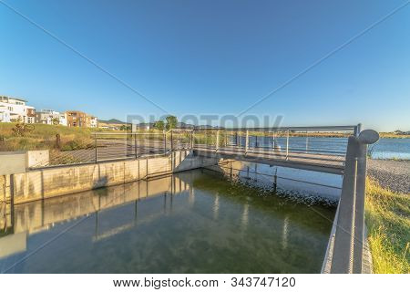 Bridge Over Lake With Lakefront Buildings And Mountain View Under Blue Sky