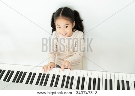 From Above Of Positive Smiling Adorable Asian Girl Practicing Music Playing Piano Relaxing In House
