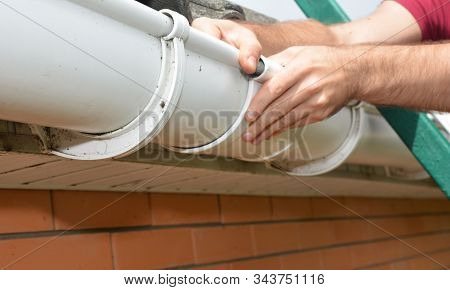 Guttering, Gutters, Plastic Guttering, Guttering & Drainage. Roofer Contractor Hands Installing And