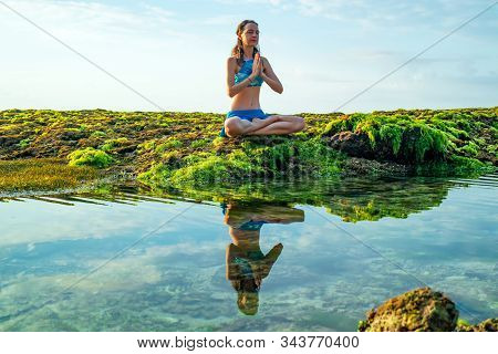 Young Woman, Meditating, Practicing Yoga And Pranayama At The Beach. Sunrise Yoga Practice. Hands In