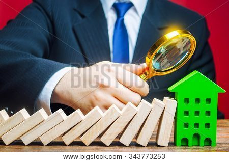 A Businessman Is Studying The Consequences Of A Domino Falling On A House. Real Estate Insurance And