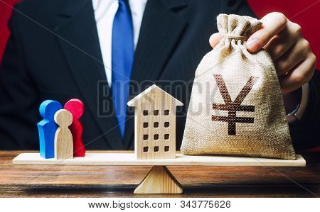 Man Puts Yen Yuan Money Bag And House On Scales With A Family. Mortgage, Debt Burden. Assistance Wit