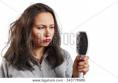 A Girl With Tousled Shaggy Hair Holds A Comb In Her Hands. Hair, Scalp And Dandruff Problems Isolate