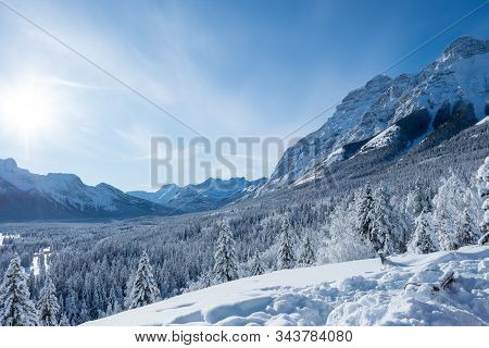 Pines And Mountains In A Valley Covered In Snow During A Winter Morning With A Clear Blue Sky In Kan