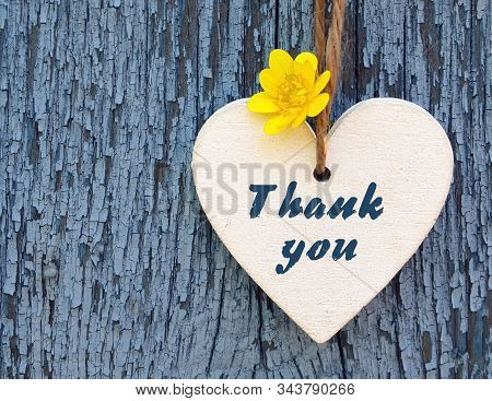Thank You Or Thanks Greeting Card With Yellow Flower And Decorative White Heart On Blue Wooden Backg