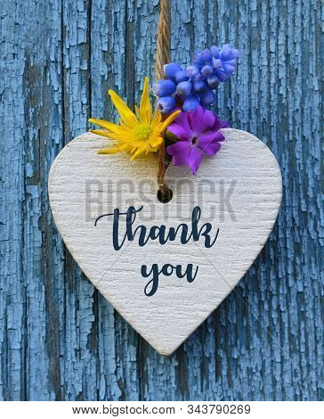 Thank You Or Thanks Greeting Card With Flowers And Decorative White Heart On Blue Wooden Background.