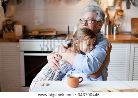 Grandmother Hug Child Girl. Kid And Senior Woman Baking In Cozy Home Kitchen. Happy Family Enjoying