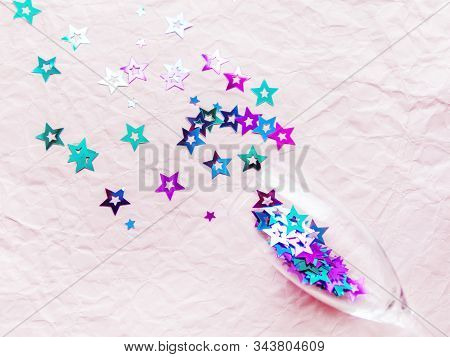 Transparent Wine Glass With Magenta And Cyan Colored Spangles. Festive Copy Space With Crockery On C