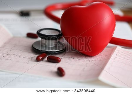 Close-up View Of Red Heart Stethoscope And Medications. Clinical Equipment On Echocardiogram Results