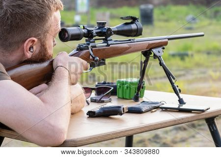A Man With A Beard Looks Into The Scope Of A Sniper Rifle, Prepares To Shoot