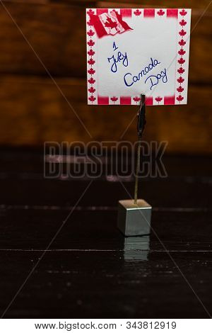 Square Memo Holder With Memo Post Reminder. Writing 1 July, Canada Day On Paper With Canada Flag. Bu