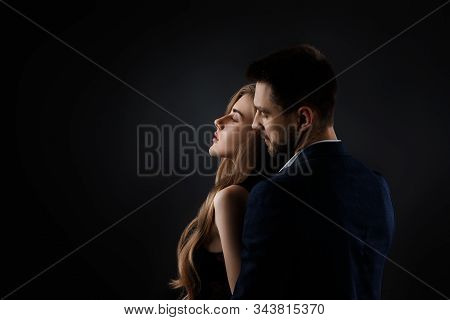 Elegant Couple On Black Background. Man Embracing Beautiful Woman In Black Dress. Copy Space
