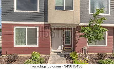 Pano Townhouse Facade With Red And Gray Wall And Bench By The Front Door And Window