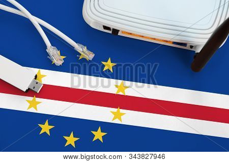 Cabo Verde Flag Depicted On Table With Internet Rj45 Cable, Wireless Usb Wifi Adapter And Router. In
