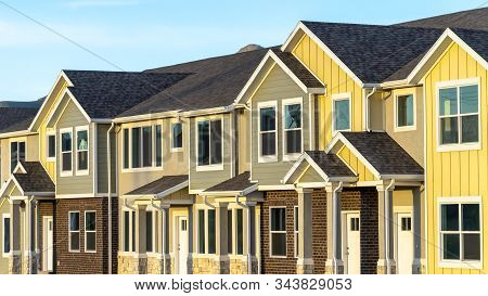Pano Frame Exterior View Of Townhomes With Gable Roof Stairs And Square Columns At Entrance