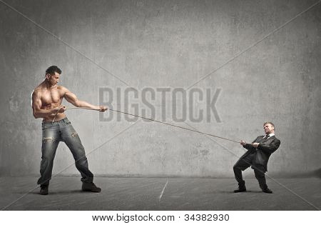 Tiny businessman and giant muscular man playing tug of war
