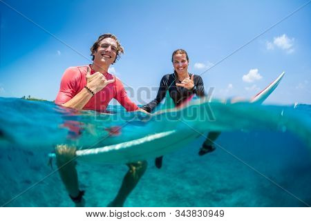 Young happy surfers man and woman sit on the surfboards in the water