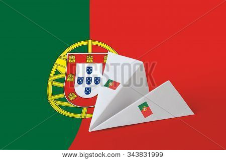 Portugal flag depicted on paper origami airplane. Handmade arts concept poster