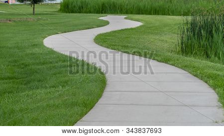 Pano Frame Narrow Paved Pathway Winding Through Lush Green Grasses Of Park With Playground