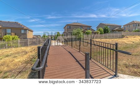 Pano Frame Bridge Over Grassy Terrain Leading To Houses With Sunny Blue Sky Background