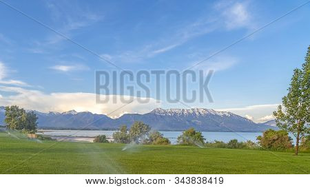 Pano Lake And Snow Capped Mountain With Sprinklers On Green Grasses In Foreground
