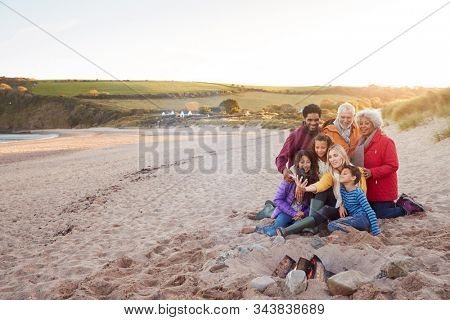 Wide Angle Shot Of Multi-Generation Family Sitting By Fire On Winter Beach Vacation Taking Selfie