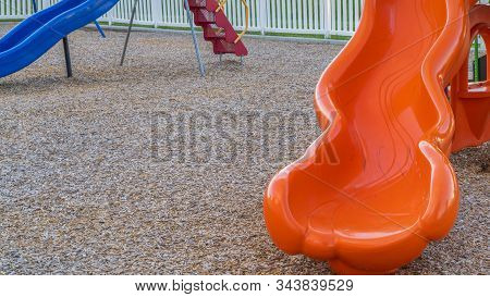 Pano Frame Close Up Of Bright And Shiny Orange Slide At A Park With Childrens Playground